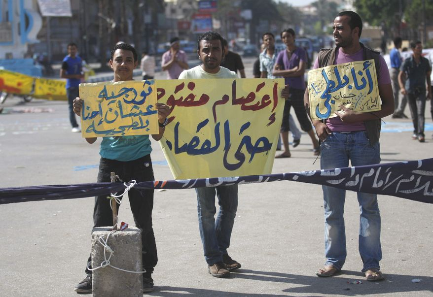 "Protesters in Martyrs Square in Suez, Egypt, on Tuesday, July 5, 2011, demonstrate with placards that read in Arabic, ""Open strike there is retribution"" (center); ""I'm a thug"" (right), which ridicules official accusations that protesters are violent thugs; and ""Revolutionaries but they call us thugs."" (AP Photo/Khalil Hamra)"