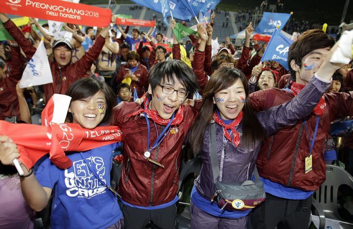 South Koreans celebrate at a ski-jumping hill in Pyeongchang, South Korea, early on Thursday, July 7, 2011, after the International Olympic Committee announced that the South Korean city will host the 2018 Winter Olympics. (AP Photo/Lee Jin-man)