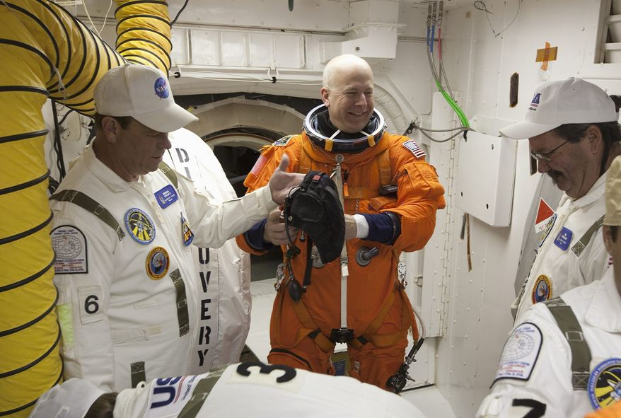 """SCOTT ANDREWS On Launch Pad 39a at NASA's Kennedy Space Center in Florida, Commander Alan G. Poindexter (center) prepares to enter Space Shuttle Discovery from the pad's """"white room"""" on April 5, 2010. Photographer Scott Andrews took many such candid shots."""