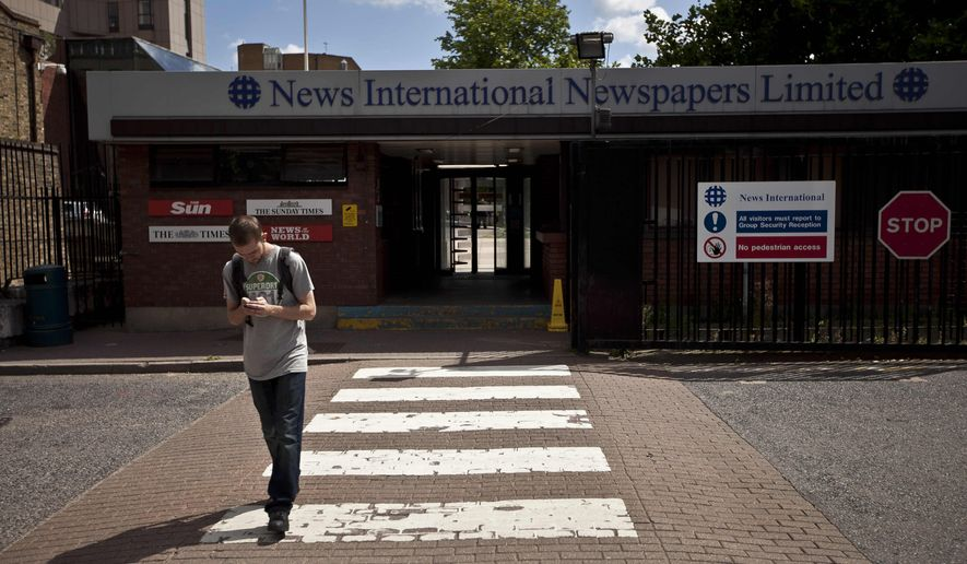 A man looks at a phone in front of a News International building in London on July 6, 2011. (Associated Press)