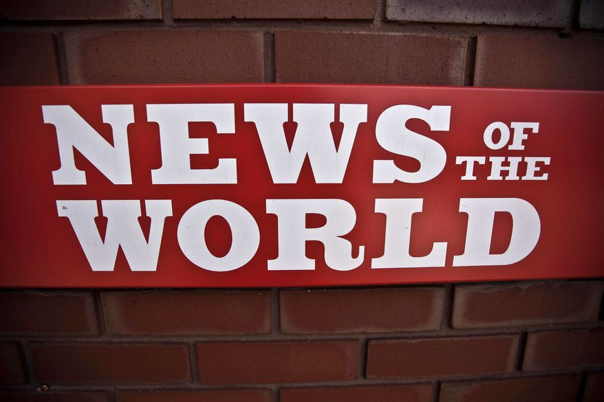 ** FILE ** A News of the World sign is seen by an entrance to a News International building in London on July 6, 2011. (Associated Press)