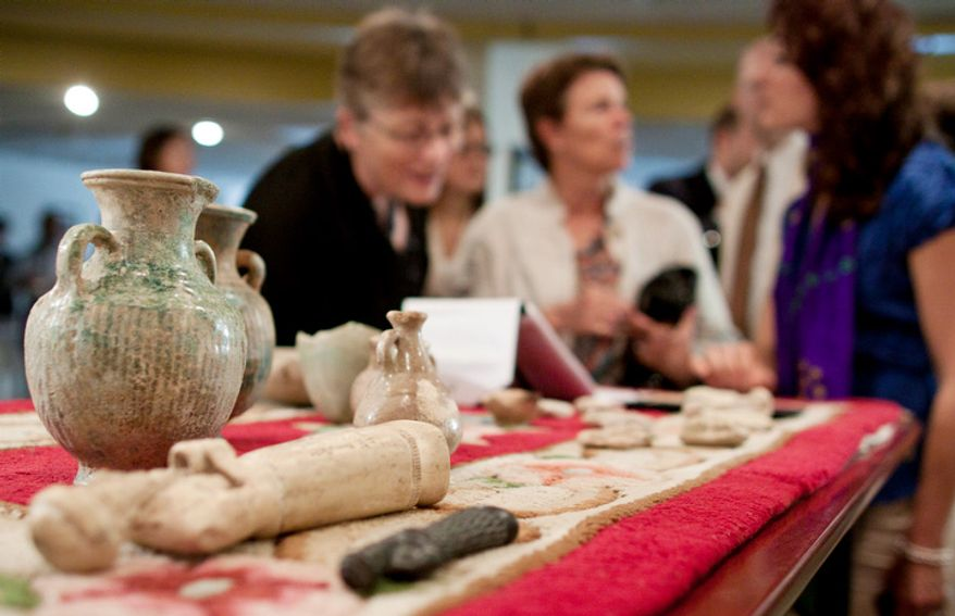 Guests and members of the press look at a table of artifacts. The illegally imported artifacts were discovered and seized as part of investigations by the U.S. Department of Homeland Security. (Pratik Shah/The Washington Times)
