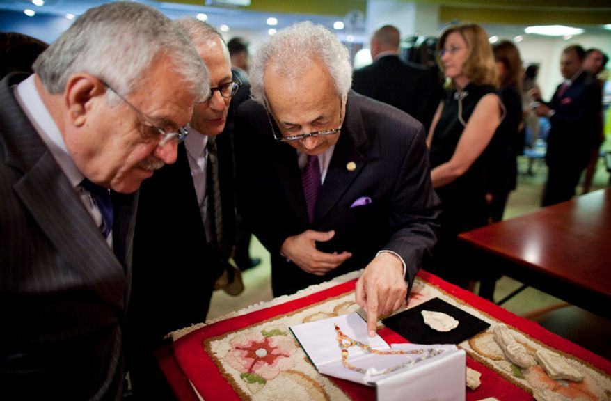 Samir Shakir Mahmood Sumaida'ie (right), Iraqi ambassador to the United States, looks closely at a Western Asiatic necklace (circa third to second millennium B.C.) during a repatriation ceremony of Iraqi antiquities at the Iraqi Cultural Center in Washington on Thursday, July 7, 2011. (Pratik Shah/The Washington Times)