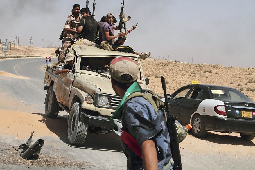 In this photo from July 6, 2011, rebels are seen on their way back from the front line after a six-hour battle in which they succeeded to liberate al-Qawalish, 60 miles southwest of Tripoli, Libya. (Associated Press)