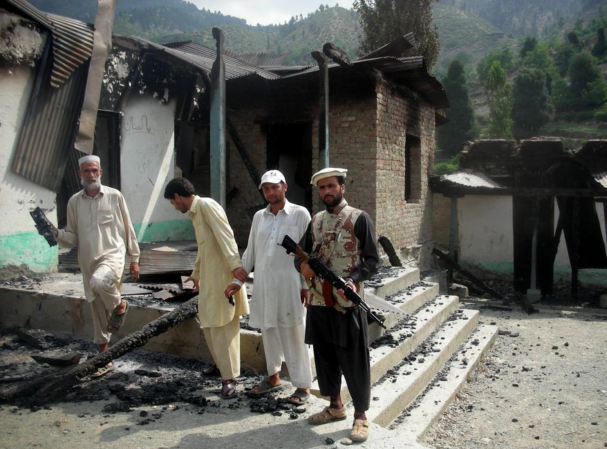 A member of a Pakistani tribal militia stands with locals outside a school gutted by militants in Nusrat Dara in Dir, Pakistan on July 7, 2011. (Associated Press)
