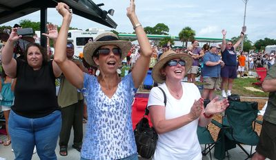 Old friends, Denise McCabe, of Vero Beach, Fla., center left and Cheryl Giesa, or Northville, Mich., cheer as they watch the Space Shuttle Atlantis, STS-135, launch from Pad 39A at Kennedy Space Center from the roadside in Titusville, Fla., seven miles away, to begin the final mission of the Space Shuttle program, Friday, July 8, 2011. (J.M. Eddins, Jr./The Washington Times)