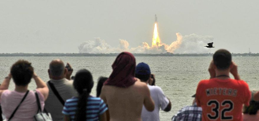 Onlookers in Titusville, Fla., watch from the roadside on Friday, July 8, 2011, as the space shuttle Atlantis launches from Pad 39A at the Kennedy Space Center, about seven miles away. (J.M. Eddins Jr./The Washington Times)