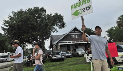 Eli Villaverde (right) of Orlando, Fla., sells parking spots on Friday, July 8, 2011, at his family's property in Titusville, Fla., about seven miles from the Kennedy Space Center, where the space shuttle Atlantis launched that morning. (J.M. Eddins Jr./The Washington Times)