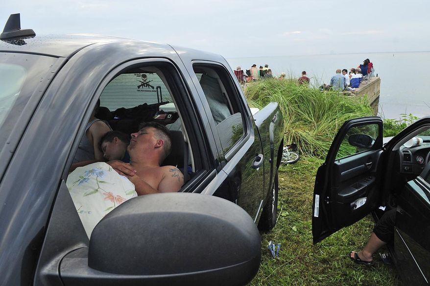 Hundreds of thousands of people watched from the roadside in Titusville, Fla., on Friday, July 8, 2011, as the space shuttle Atlantis launched from Pad 39A at the Kennedy Space Center, about seven miles away. Some claimed a spot the night before and slept in their vehicles while awaiting the launch. (J.M. Eddins Jr./The Washington Times)