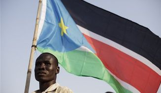 A Bari community member holds the flag of southern Sudan during celebrations on the eve of their declaration of independence in Juba, southern Sudan, Friday, July 8, 2011. Southern Sudan is set to declare independence from the north on Saturday. (AP Photo/David Azia)