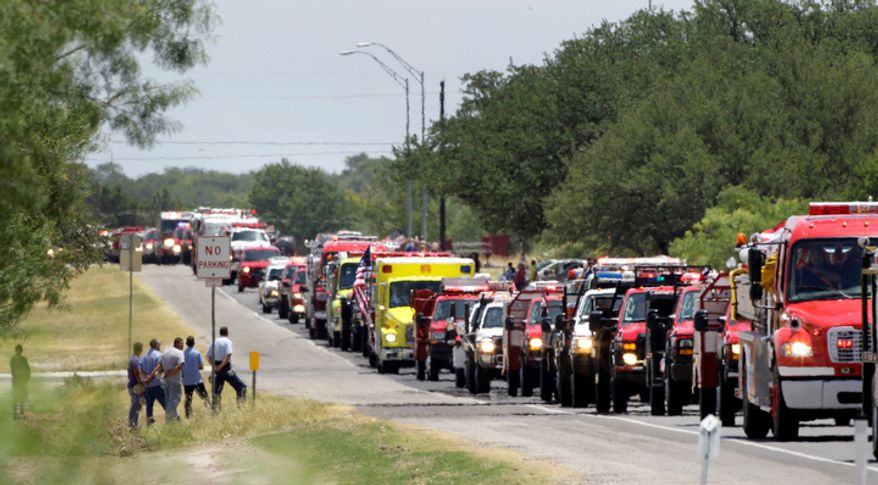 People stand on the side of the road as emergency vehicles in a funeral processional for Brownwood firefighter Lt. Shannon Stone make their way down the road in Brownwood, Texas. (AP Photo/Tony Gutierrez)