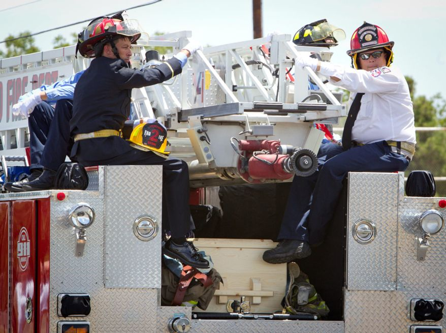 Firefighters sit at the back of the fire truck carrying the casket of  Brownwood firefighter Shannon Stone on the way to the cemetary after his funeral.  (AP Photo/Star-Telegram, Joyce Marshall)