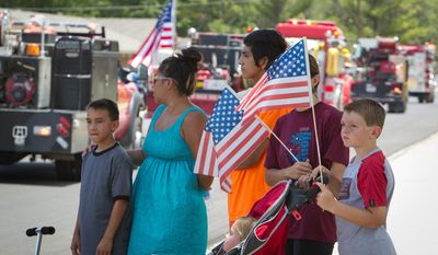 John Hammond, Tammy Contreras, Jesse Jauregui, Jessica Rudloff, Jaden Rudloff  and Jayli Rudloff,  in the stroller,  stand along the route of the procession to honor Brownwood firefighter Shannon Stone in Brownwood on Monday, July 11,  2011.  (AP Photo/Star-Telegram, Joyce Marshall)