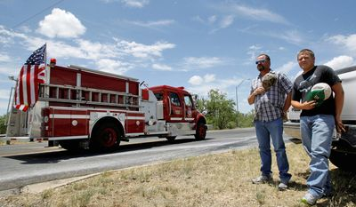 Area residents Steve and Ky McDorman stand by the roadside as a funeral procession of emergency vehicles for Lt. Shannon Stone of the Brownwood Fire Department drives by on Monday, July 11, 2011  (AP Photo/Tony Gutierrez)