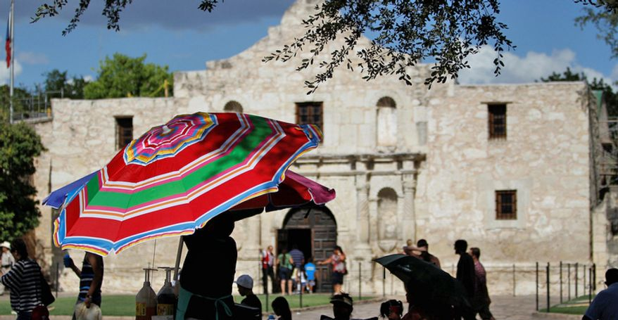 A vendor near the Alamo opens a umbrella to provide protection from the sun, Monday, July 11, 2011, in San Antonio, Texas. (AP Photo/Eric Gay)