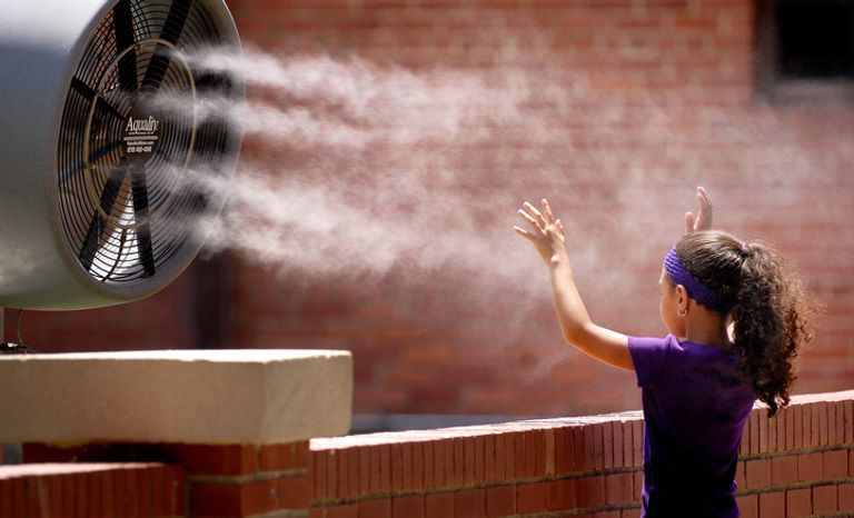 Andre Rivera, 6, from Puerto Rico, stops in front of a misting fan at the Fort Worth Stockyards. (AP Photo