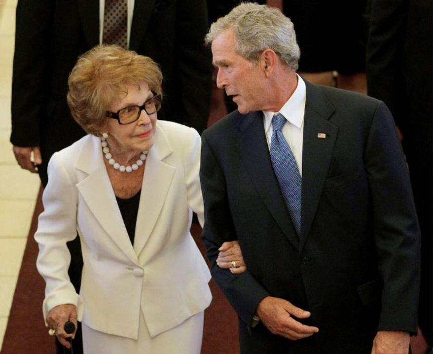 Former first lady Nancy Reagan, left, is escorted by former President George W. Bush following the funeral for former first lady Betty Ford at St. Margaret's Episcopal Church Tuesday, July 12, 2011, in Palm Desert, Calif.  (AP Photo/Jae C. Hong, Pool)