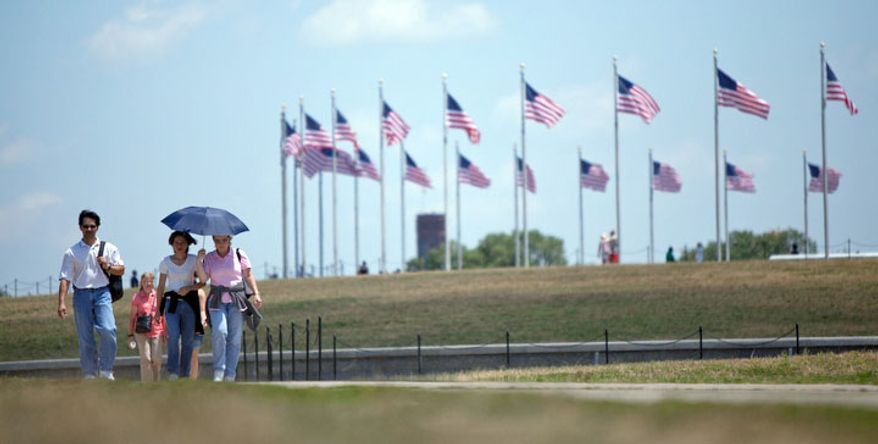 Happy Sermsri, from Thailand, and Betty Giarratana, from Fredericksburg, Va. stay cool under an umbrella near the Washington Monument in Washington, D.C. on Tuesday, July 12, 2011. (Pratik Shah/The Washington Times)