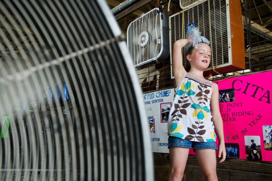 Abigail Gregory, 7, holds an ice bag on her head as she leans up against fans set up in the horse barn at the Bartholomew County 4-H Fair near Columbus, Ind.    (AP Photo/The Republic, Alton Strupp)