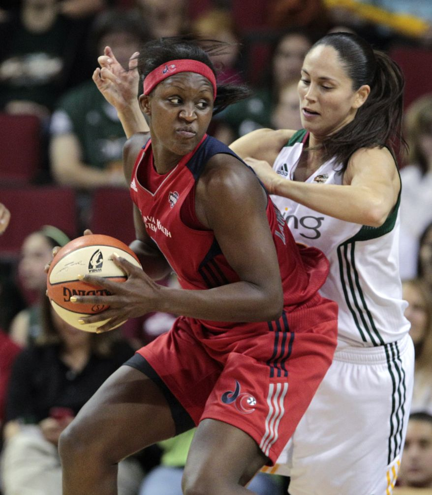 Washington Mystics' Crystal Langhorne, left, tries to put a move on Seattle Storm's Sue Bird in the first half of a WNBA basketball game Tuesday, July 12, 2011, in Seattle. The Storm won 79-71. (AP Photo/Elaine Thompson)
