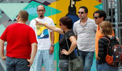 Kit Sullivan (center), of Roam Rides, talks about outdoor art during a two-hour graffiti tour in Wynwood. Artists looking for a space to paint legally here may seek help from Primary Flight, an organization that has brought hundreds of artists to the streets of the neighborhood. (Associated Press)