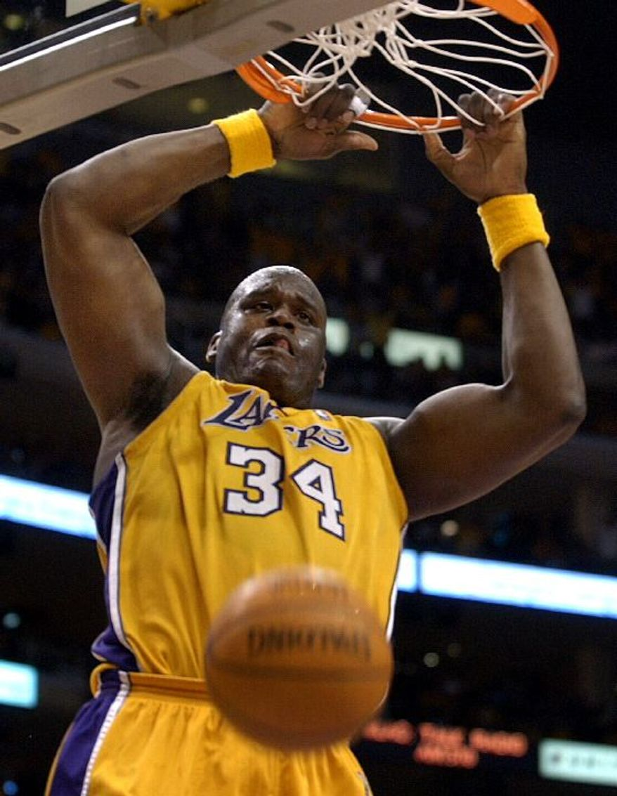Los Angeles Lakers' Shaquille O'Neal hangs from the rim after a slam dunk in the fourth quarter of Game 1 of their Western Conference semifinal series against the San Antonio Spurs in Los Angeles, Sunday, May 5, 2002. The Lakers won the game 86-80. (AP Photo/Kevork Djansezian)