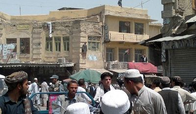 ASSOCIATED PRESS PHOTOGRAPHS The lifeless body of Sardar Mohammad, who assassinated Ahmed Wali Karzai, the half-brother of Afghanistan's president, hangs briefly from a building Tuesday in Charso Chowk, Kandahar province.