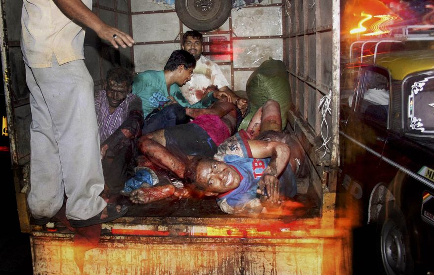 Injured victims of a bomb explosion are loaded onto a truck to be taken to hospital at Zaveri bazar in Mumbai, India, on July 13, 2011. Three explosions hit busy locations in India's business capital of Mumbai, where a terror siege nearly three years ago killed 166 people. (Associated Press)