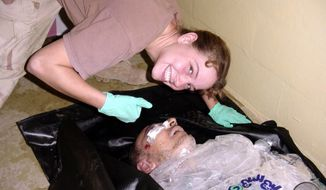 ** FILE ** Army Spc. Sabrina Harman of the 372nd Military Police Company poses with the body of Iraqi detainee Manadel al-Jamadi, who is packed in ice, at the Abu Ghraib prison in Baghdad in 2003. (Associated Press/ABC News)