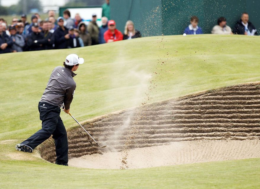 ASSOCIATED PRESS Rory McIlroy plays a shot out of the bunker on the 15th hole. McIlroy carded a 1-over 71 on Thursday.