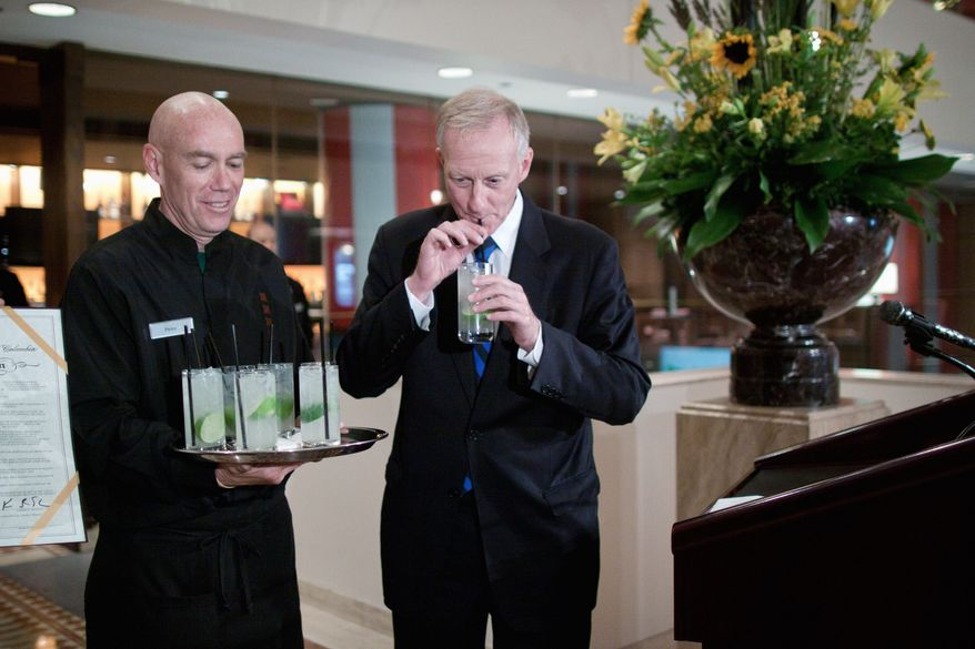 """D.C. Council member Jack Evans (right) takes a sip of a """"Rickey"""" cocktail, which he said was enjoyed by congressmen in the 19th century. He sampled it at the JW Marriott in the District on Thursday. (Pratik Shah/The Washington Times)"""