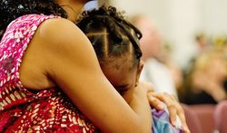 Miriam Carter of Ocoee, Fla., comforts her 6-year-old daughter, Liana, during the National 9/11 Flag stitching ceremony Thursday on Capitol Hill. Ms. Carter's sister, Maria Ramirez, was killed in the Sept. 11, 2001, attack in New York City. (Barbara L. Salisbury/The Washington Times)