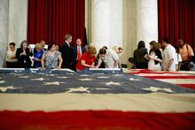People line up to stitch the National 9/11 Flag during a special ceremony Thursday at the Russell Senate Office Building. The flag is on tour countrywide to be mended in time for the 10th anniversary of the Sept. 11, 2001, terrorist attacks. (Barbara L. Salisbury/The Washington Times)