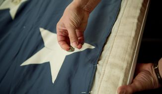 SPECIAL STITCHES: A woman stitches some of the blue fabric of the National 9/11 Flag during a ceremony to honor the victims. The flag was flying just south of the World Trade Center on Sept. 11, 2001. (Barbara L. Salisbury/The Washington Times)