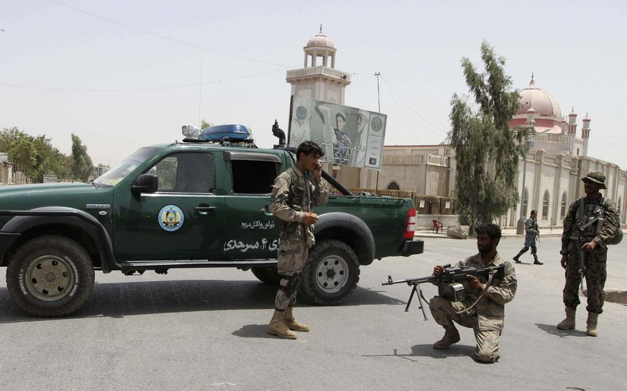 Afghan police men stand guard outside the mosque after a suicide attack in Kandahar, Afghanistan, on July 14, 2011. The bomber blew himself up inside the mosque during a memorial service for the assassinated half brother of Afghan President Hamid Karzai, killing four people, the government said. (Associated Press)