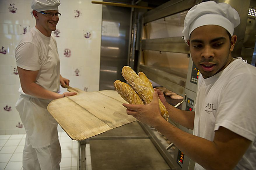 Bakers Frederic Lafrenoy (left) and Francisco Angulo unload loaves of freshly baked baguettes at Paul Bakery in Washington, D.C., Thursday, July 14, 2011. Some of these loaves will be used in the Baguette Relay Races, held at  the United States Navy Memorial, to honor Bastille Day. (Rod Lamkey Jr/The Washington Times)