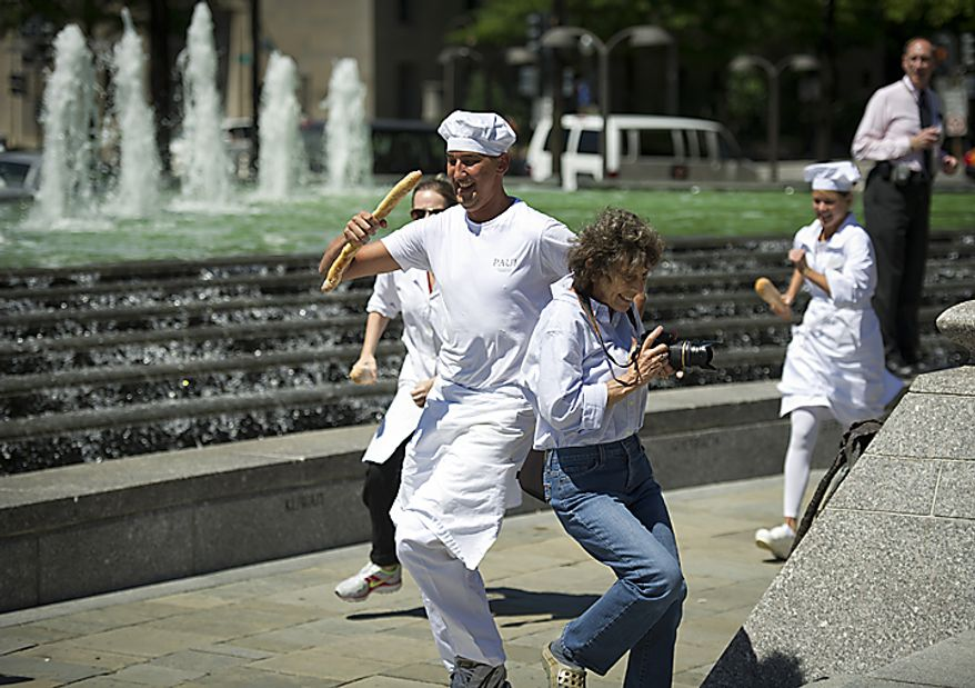 A photographer gets in the way as Paul Bakery bakers Malik Ayed (center) Laetitia Steinier (partially hidden at left) and Casey Hanley (right) make their way around the United States Navy Memorial in the Baguette Relay Races, to honor Bastille Day in Washington, D.C., Thursday, July 14, 2011. The races were sponsored by Paul Bakery. (Rod Lamkey Jr/The Washington Times)