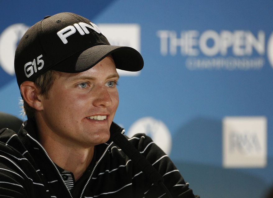 England's Tom Lewis smiles during a press conference after his round (in which he shot a 65) on the first day of the British Open Golf Championship at Royal St George's on Thursday. He currently is tied for first place with Thomas Bjorn.  (AP Photo/Jon Super)
