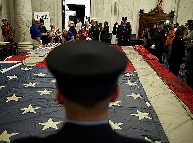 A New York City police officer stands guard over the official 9/11 National flag at the Russell Senate Office Building in Washington, D.C., on Thursday, July 14, 2011. The flag was in the nation's capital for a stitching ceremony in which members of Congress, 9/11 families, first responders and the general public were all invited to add stitches to help complete the flag. This flag was flying just south of the World Trade Center on Sept. 11, 2001 and is now being stitched back together by Americans from across the country, many of whom have suffered tragedies of their own. Where pieces are missing, people are adding their own pieces, including entire flags and a piece of the flag that cradled Pres. Abraham Lincoln after he was shot. (Barbara L. Salisbury/The Washington Times)