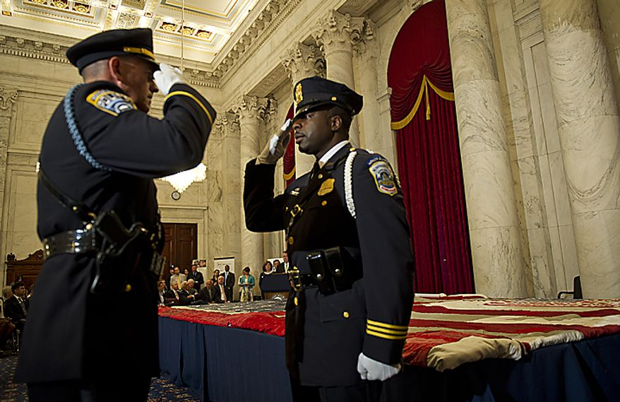 ** FILE ** Two U.S. Capitol Police officers exchange salutes as they change command while guarding the official 9/11 National flag during a stitching ceremony in the Kennedy Caucus Room in the Russell Senate Office Building in Washington, D.C., on Thursday, July 14, 2011. An American flag that was flying just south of the World Trade Center in New York City on Sept. 11, 2001, is making its way around the country and being stitched back together. (Barbara L. Salisbury/The Washington Times)