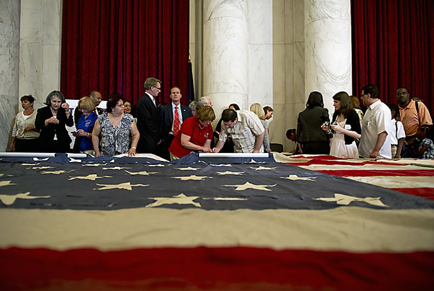 People line up to stitch the official 9/11 National flag during a stitching ceremony Thursday, July 14, 2011 at the Russell Senate Office Building in Washington, D.C. This flag, which was flying just south of the World Trade Center on Sept. 11, 2001, is making its way around the country and is being stitched back together by Americans, many of whom have suffered their own tragedies. Where pieces of the original flag are missing, people are adding their own pieces, including a piece of the flag that was laid under Pres. Abraham Lincoln after he had been shot. (Barbara L. Salisbury/The Washington Times)