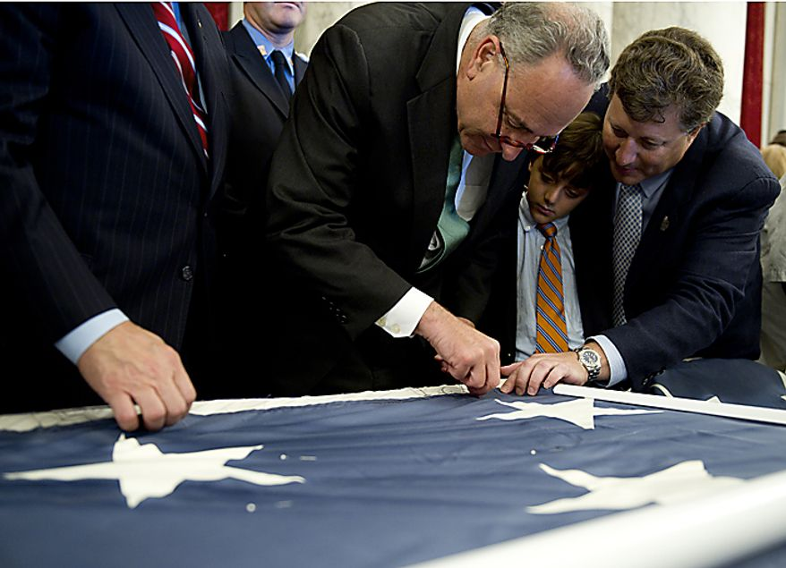 Sen. Charles Schumer (D-N.Y.), left, stitches on the official 9/11 National flag while Jeff Parness, founder and chairman of the New York Says Thank You Foundation and his son, Josh, look on. The flag was at the Russell Senate Office Building in Washington, D.C., on Thursday, July 14, 2011. This flag was flying south of the World Trade Center in New York City on Sept. 11, 2001, and now it is making its way around the country and is being stitched back together by Americans. When it is completed, it will hang in the official Sept. 11 memorial in New York City. (Barbara L. Salisbury/The Washington Times)