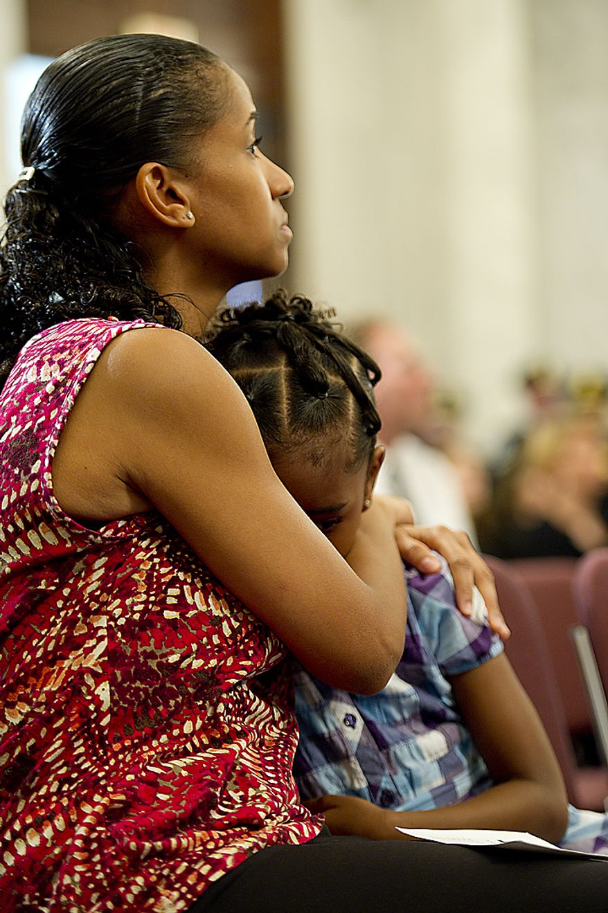 Miriam Carter of Ocoee, Fla., comforts her 6-year-old daughter Liana during the 9/11 National Flag Stitching Ceremony, held in the Kennedy Caucus Room in the Russell Senate Office Building in Washington, D.C., on Thursday, July 14, 2011. Carter's sister Maria Ramirez was killed in the Sept. 11 attack in New York City. An American flag that was flying just south of the World Trade Center in New York City on Sept. 11, 2001 is making its way around the country and being stitched back together. The goal is to have the flag completed by this Sept. 11, in time for the 10th memorial. The finished flag will be on display at the official 9/11 Memorial in New York City. (Barbara L. Salisbury/The Washington Times)