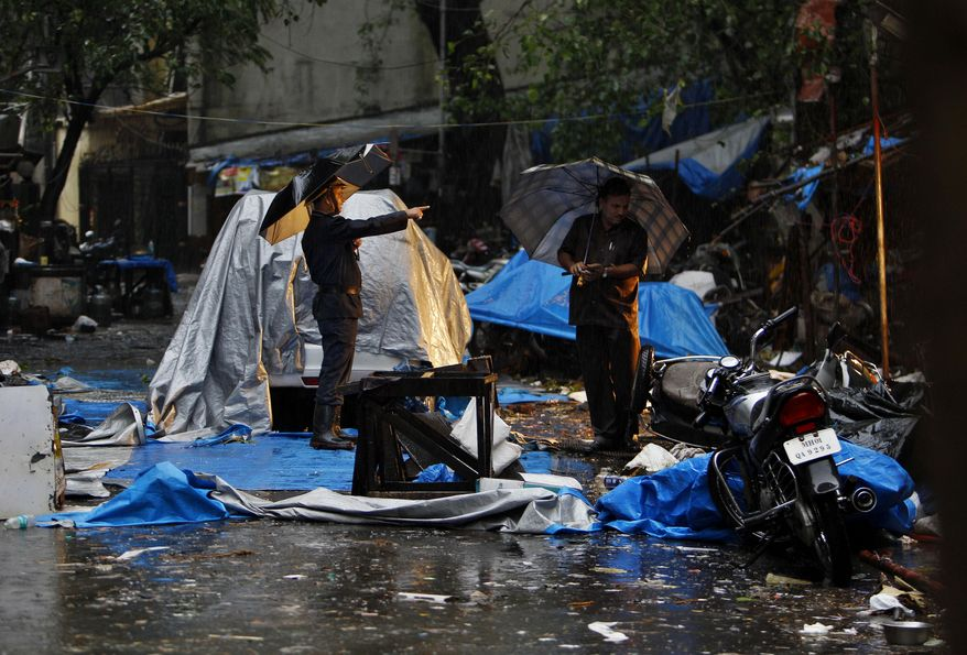 Indian police officers inspect debris covered by blue sheets in Mumbai, India, on July 14, 2011, at the Opera House, one of three sites where an explosion happened the day before. (Associated Press)