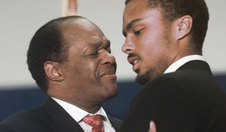 ** FILE ** Then-D.C. Mayor Marion Barry hugs his son, Christopher, in 1998. (Associated Press)
