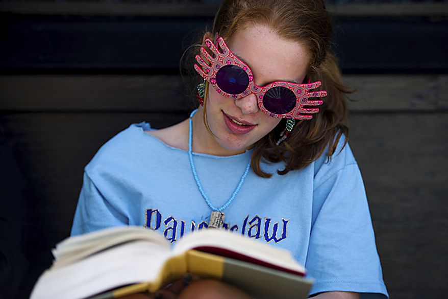 Julia Smith, 14, sports her Luna Lovegood (character from the series) sunglasses and homemade earrings while she reads the seventh Harry Potter book as she waits for the midnight start of the final Harry Potter movie, near the Uptown Theater along Connecticut Ave. in Cleveland Park, in Washington, D.C., Thursday, July 14, 2011. (Drew Angerer/The Washington Times)
