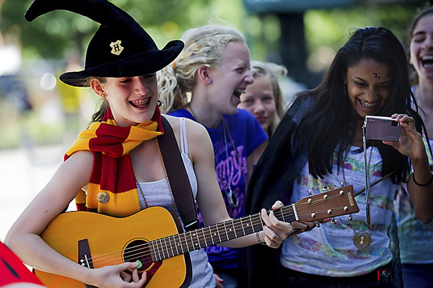 "At left, Sofia Roma, 14, of the District, plays and sings ""Goin' Back to Hogwarts,"" a song from ""A Very Potter Musical,"" while her and her friends wait for the midnight start of the final Harry Potter movie, near the Uptown Theater along Connecticut Ave. in Cleveland Park, in Washington, D.C., Thursday, July 14, 2011. ""The best part of the waiting in line experience is meeting all the other fans,"" said Roma. (Drew Angerer/The Washington Times)"