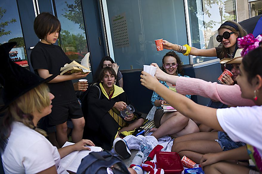 Friends raise a toast to Issac Sarnoff, 14, (center in black and yellow cloak) and  Lila Weitzner, 13, (right of Sarnoff, in clear glasses) who made Harry Potter drinks Butter Beer and Pumpkin Juice, as they wait for the midnight start of the final Harry Potter movie, near the Uptown Theater along Connecticut Ave. in Cleveland Park, in Washington, D.C., Thursday, July 14, 2011. They arrived at 11am and bought tickets for the show over two months ago. (Drew Angerer/The Washington Times)