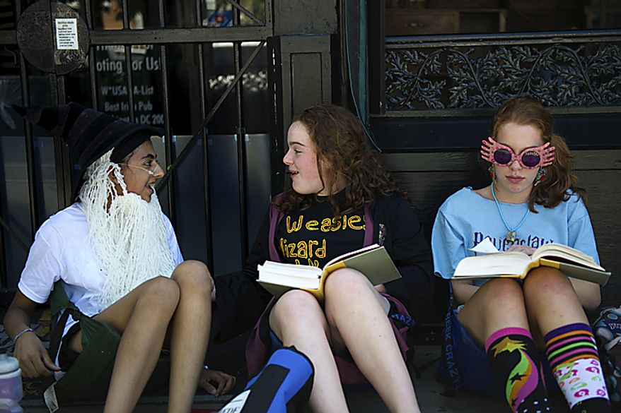 "From left, Afriti Bankwalla (dressed as Professor Dumbledore), 14, Laura Smith (dressed as Rose Weasley), 14, and Julia Smith (dressed as Luna Lovegood), 14, hang out and read the final Harry Potter book as they wait for the midnight start of the final Harry Potter movie, near the Uptown Theater along Connecticut Ave. in Cleveland Park, in Washington, D.C., Thursday, July 14, 2011. ""It's great to meet all these other Harry Potter fans,"" said Bankwalla. ""There's never this many fans in one place."" (Drew Angerer/The Washington Times)"