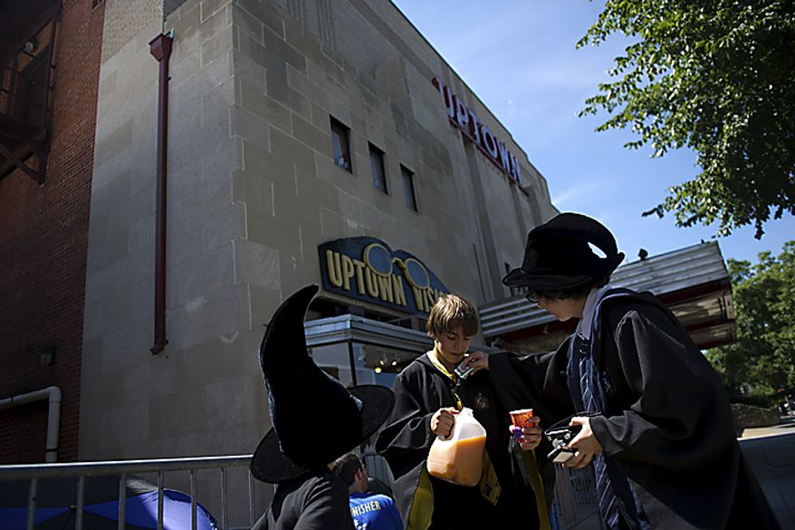 In the center, Isaac Sarnoff, 14, sells Pumpkin Juice (a favorite drink in the Potter series) to Nina Cohen, right, as they wait for the start of the midnight showing of the final Harry Potter movie near the Uptown Theater along Connecticut Ave. in Cleveland Park, in Washington, D.C., Thursday, July 14, 2011. Sarnoff also made Butter Beer, which he made by mixing root beer and butter. (Drew Angerer/The Washington Times)